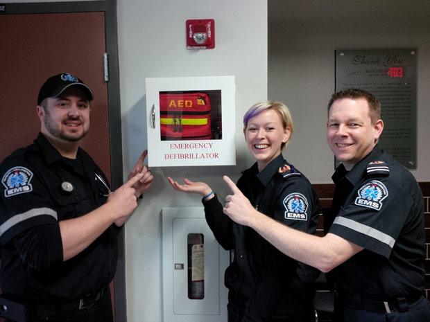 3 members of Guelph Wellington EMS pointing at a public emergency defibrillator.