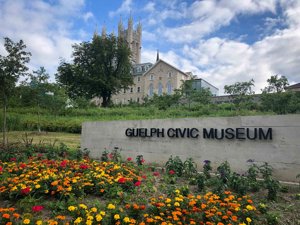 garden with red, orange and yellow marigolds and museum in background
